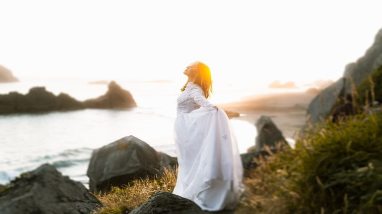 Woman taking a deep breath overlooking a rocky beach