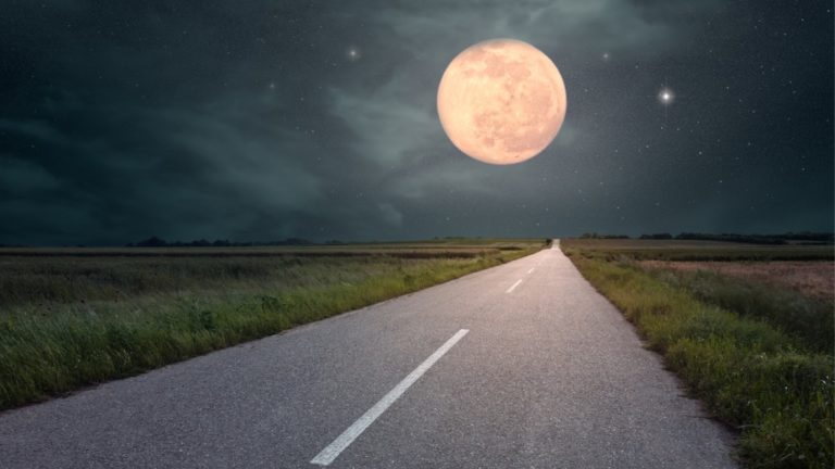 driving-on-an-empty-road-towards-the-moon-picture-id500460955