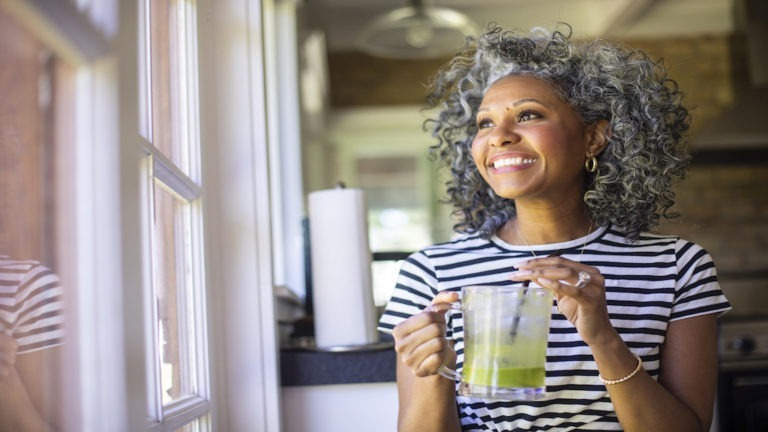 A beautiful black woman with white curly hair drinks a green smoothie in the morning for breakfast.
