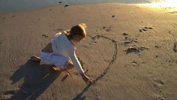 Child playing on the beach drawing a heart in the sand