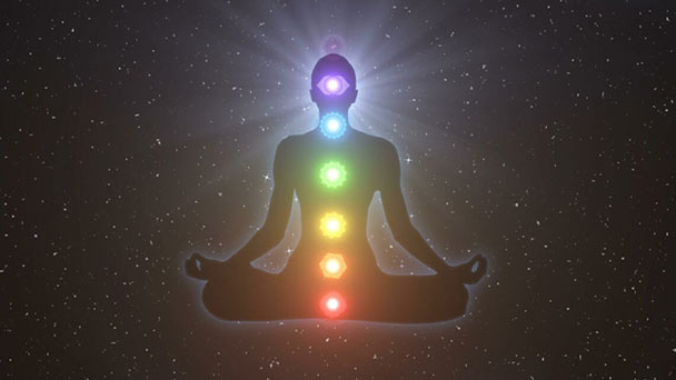 Graphic with seated person's silhouette in meditation with seven chakras floating at top