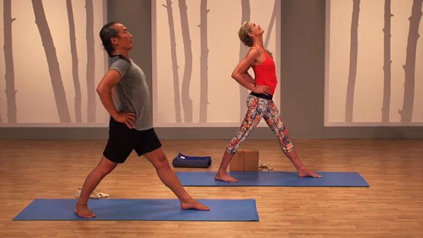 Yoga studio with two yogis in forward poses