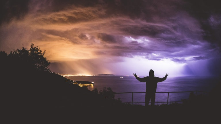 Silhouette of person standing on balcony terrace with fence looking open hands toward flashing thunderstorm cloudscape above Gulf of Trieste - Adriatic sea in Friuli Venezia Giulia region of Italy.
