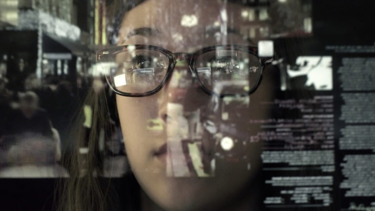 An asian woman concentrating on a touch screen display. The point of view is from behind the screen, looking through the data & images to the woman's face and hands as she manipulates the windows of information.