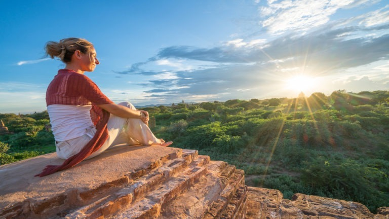 Caucasian young woman contemplating the Bagan archeological zone at sunrise, temples pagodas and monastery coming out from the lush greenery. People travel concept.