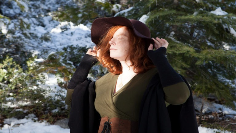 Red-haired adult women wearing a green dress and cloak in a snow covered forest.  She has a witch-like appearance.