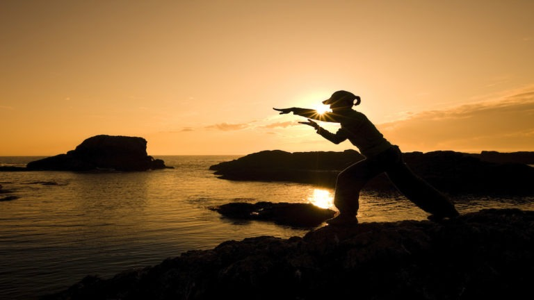 Woman practicing meditation-martial arts on a rocky ocean shore with the warm colors of the Sun in the background.