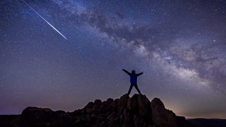 Man with Bright shooting star under Milky Way Galaxy